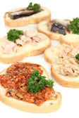 Tasty sandwiches with tuna and cod liver sardines different kinds of canned fish, isolated on white — Stock Photo
