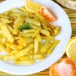 Ruddy fried potatoes on plate on tablecloth close-up — Стоковая фотография