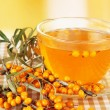 Branches of sea buckthorn with tea on tablecloth on bright background — Stock Photo