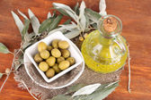 Olives in bowl with branch on sackcloth on wooden table — Stock Photo
