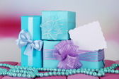Gift boxes with blank label and chaplet on table on bright background — Foto Stock