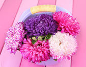 Bright aster flowers in basket on bright wooden background — Stock Photo