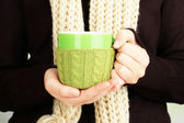 Cup with knitted thing on it in female hands close up — Stockfoto