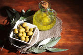 Olive oil and olives in bowl on sackcloth on wooden table — Stock Photo