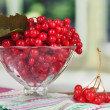 Red berries of viburnum in glass vase on table on bright background — Stock Photo