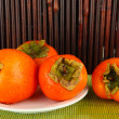 Stock Photo: Ripe persimmons on plate on table on bamboo background
