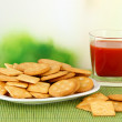 Delicious crackers with tomato juice on bamboo mat on bright background — Stock Photo