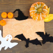 Old paper with Halloween decorations on grey wooden background — Stock Photo #35345243