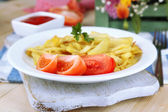 Ruddy fried potatoes on plate on wooden table close-up — ストック写真