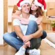 Young couple with boxes in new home celebrating New Years — Stock Photo #35354977