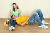 Joven pareja descansando de renovación en piso nuevo — Foto de Stock