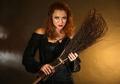 Halloween witch with broom on dark background — Stock Photo