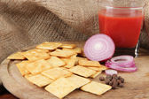 Delicious crackers with onion and tomato juice on wooden table on sackcloth background — Stock Photo