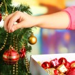Decorating Christmas tree on bright background — Stock Photo #35378937