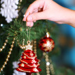 Decorating Christmas tree on bright background — Stock Photo #35378965