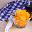 Chips in bowl, cola and TV remote on wooden table close-up — Stock Photo