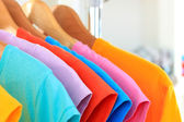Variety of casual t-shirts on wooden hangers — Stock Photo