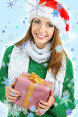 Beautiful smiling girl in New Year hat with gift — Stock Photo