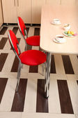 Moderne rode stoelen in de buurt van tafel in keuken — Stockfoto