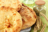 Pita breads on wooden stand with spices and spikes on tablecloth close up — Stock Photo