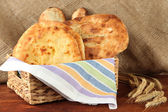 Pita breads in basket with spikes on table on sackcloth background — Stock Photo