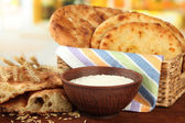 Pita breads in basket with spikes and flour on table on bright background — Stock Photo