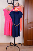 Dresses hanging on hanger near door — Stock Photo