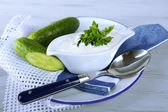 Cucumber yogurt in sauceboat, on color napkin, oncolor wooden background — Stock Photo