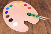 Wooden art palette with paint and brushes on table close-up — Stock fotografie