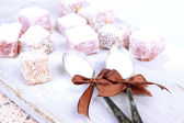 Tasty oriental sweets (Turkish delight) with powdered sugar, on wooden desk — Stock Photo