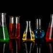 Test tubes with colorful liquids on dark grey background — Stock Photo