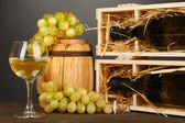 Wooden case with wine bottle, barrel, wineglass and grape on wooden table on grey background — Stock Photo