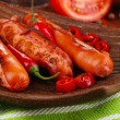 Delicious sausages with vegetables on plate on wooden table close-up — Stock Photo #35450585