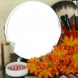 Round table mirror with cosmetics and flowers on table on wooden background — Stock Photo #35450911