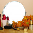 Round table mirror with cosmetics on table on beige background — Stock Photo #35450917