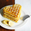 Sweet Belgium waffles with banana, on wooden table background — ストック写真