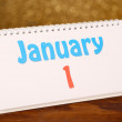 New Year calendar on wooden table, on shiny golden background — Stock fotografie