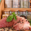 图库照片: Large piece of pork marinated with herbs and spices close-up on white table on window background
