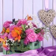 Flowers composition in crate with decorations on table on wooden background — Stock Photo