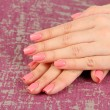 Beautiful woman hands with pink manicure, on color background — Stock Photo