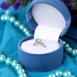 Flowers  and engagement ring on blue cloth — Stok fotoğraf