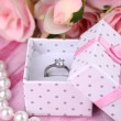 Rose and engagement ring on pink cloth — Stok fotoğraf