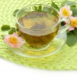 Cup of herbal tea with hip rose flowers, isolated on white — Stock Photo