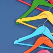Colorful clothes hangers on blue background — Stock Photo