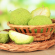 Osage Orange fruits (Maclurpomifera) in basket, on wooden table, on nature background — Stock Photo #35452741