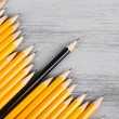Stock Photo: Celebratory pencil among usual pencils, on color background