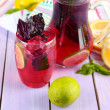 Red basil lemonade in jug and glass, on wooden background — Stock Photo