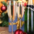 Bottle of champagne with glasses and Christmas balls on wooden table on Christmas tree background — Stock Photo