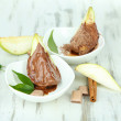 Pear slices in chocolate in bowls on wooden table — Stock Photo