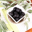 Olives in bowl with branch on napkin on wooden board on table — Stock Photo